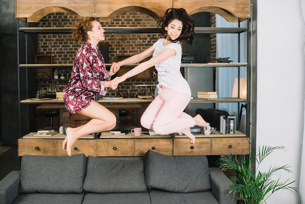 Deux jeunes femmes sautant sur un canapé à la maison