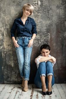 Deux jeunes femmes séduisantes aux cheveux blonds et noirs portant des jeans se tiennent près du mur