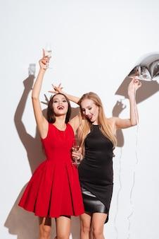Deux jeunes femmes séduisantes et heureuses buvant du champagne et faisant la fête sur fond blanc