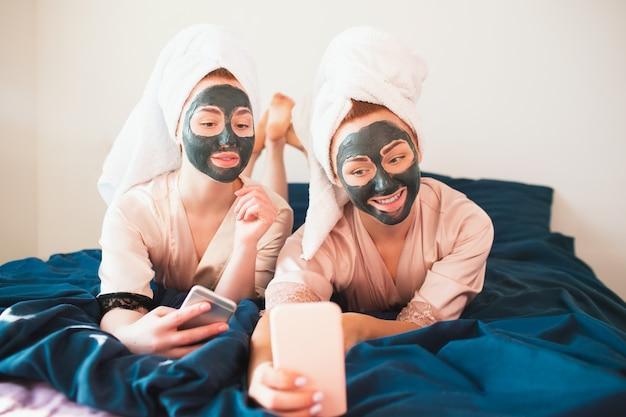 Deux jeunes femmes en serviettes et pyjamas organisent une fête de spa amusante à la maison.