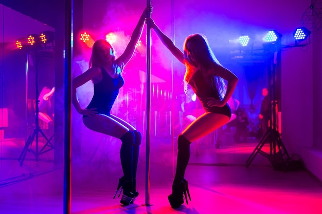 Deux jeunes femmes sexy dansent un strip-tease près du pylône.