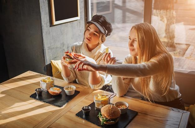 Deux jeunes femmes sont assises à l'intérieur à tabe. modèle à droite point en avant. le second tient un burger à la main. ils attendent avec impatience.