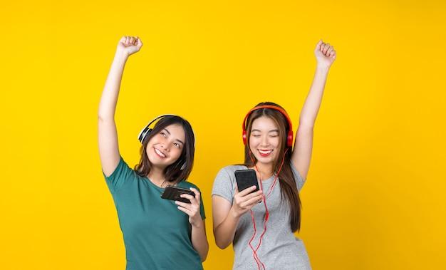 Deux jeunes femmes souriantes asiatiques de bonheur portant des écouteurs sans fil pour écouter de la musique