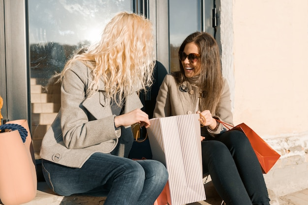 Deux jeunes femmes souriantes dans une rue avec des sacs à provisions