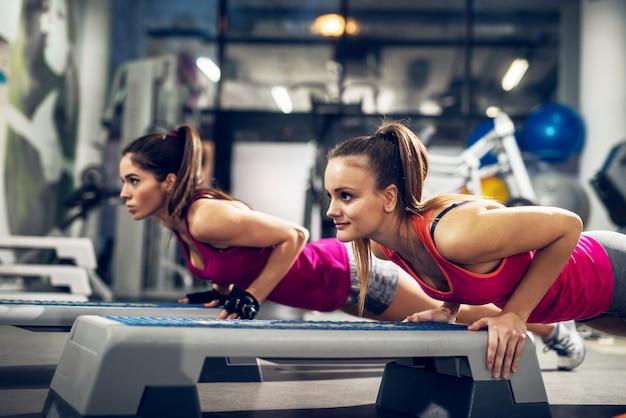 Deux jeunes femmes sportives actives axées attrayantes athlétiques motivées faisant des pompes sur des steppers dans la salle de sport moderne.