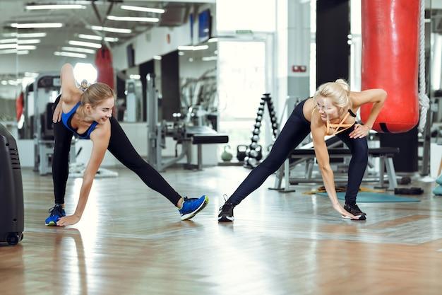 Deux jeunes femmes sportives s'entraînent ensemble dans une salle de sport