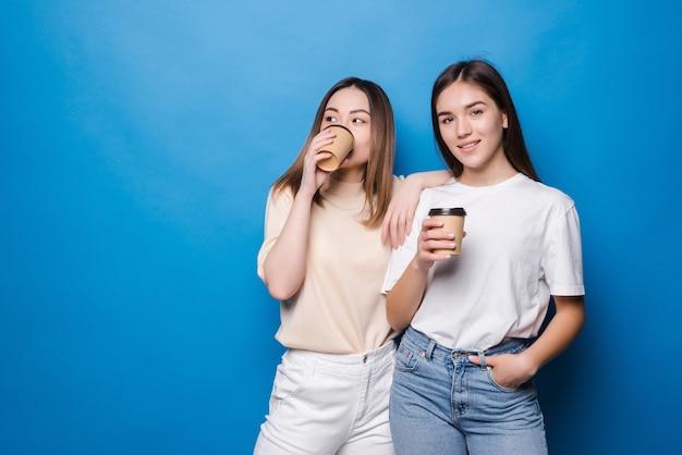 Deux jeunes femmes avec une tasse de café pour aller isolé sur un mur bleu
