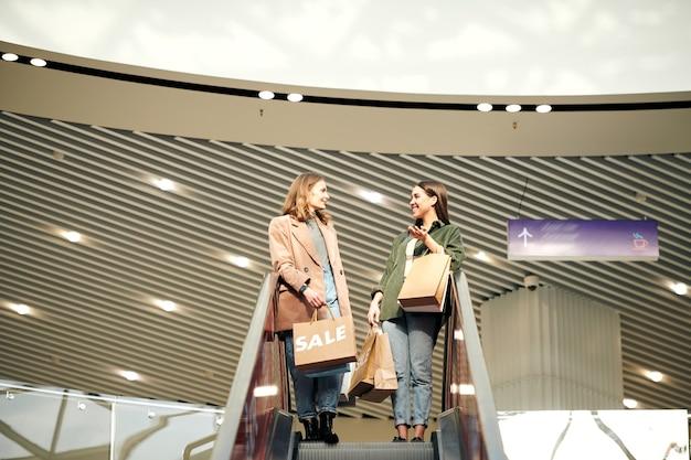 Deux jeunes femmes en tenue décontractée tenant des sacs en papier en se tenant debout sur un ascenseur et discutant de ce qu'elles ont acheté en vente dans le centre commercial
