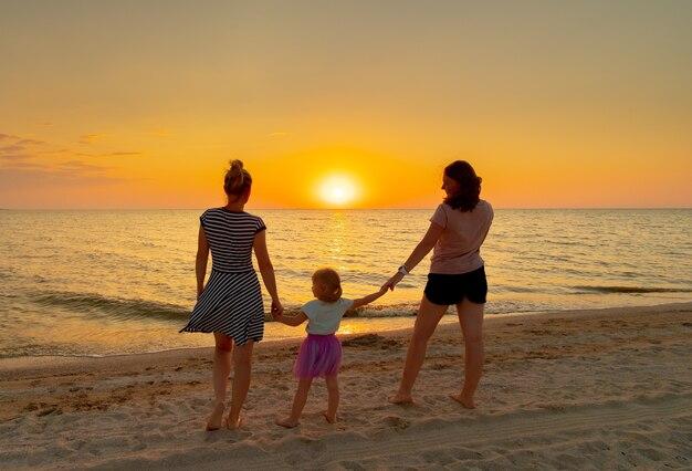 Deux jeunes femmes tiennent par la main une petite fille, debout sur la plage de la mer un soir d'été. en arrière-plan, le soleil du soir se couche à l'horizon.