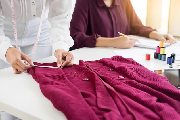 Deux jeunes femmes travaillant comme créatrices de mode et dessiner des croquis et obtient des conseils sur les tissus