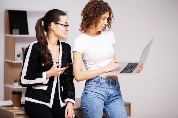Deux jeunes femmes travaillant sur un projet commun au bureau