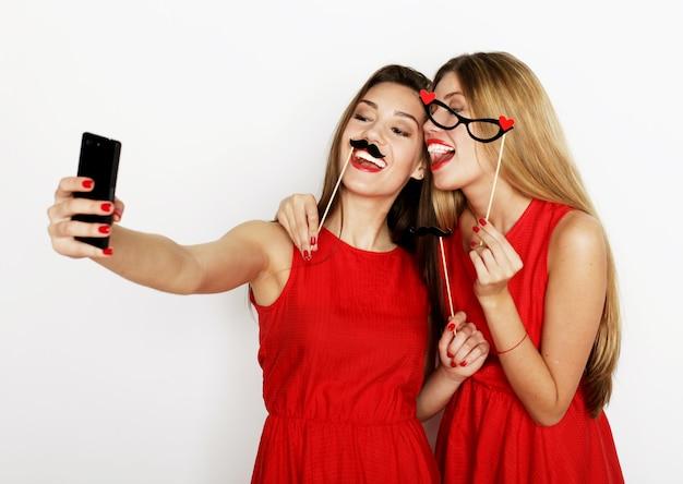 Deux jeunes femmes vêtues d'une robe rouge prenant un selfie avec un téléphone portable