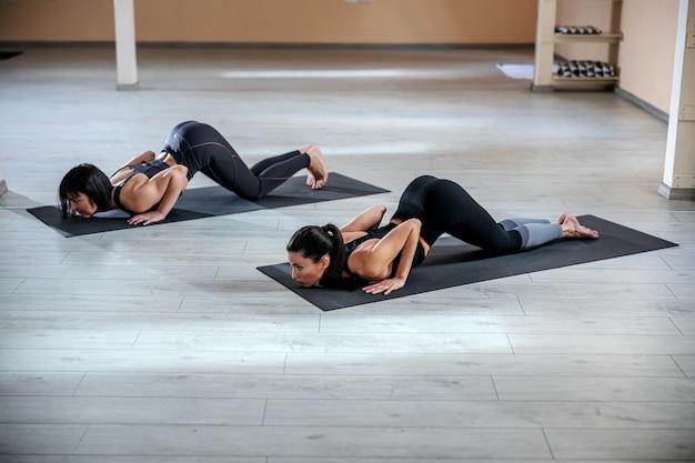 Deux jeunes femmes yogi flexibles en pose de yoga en huit points. intérieur du studio de yoga.
