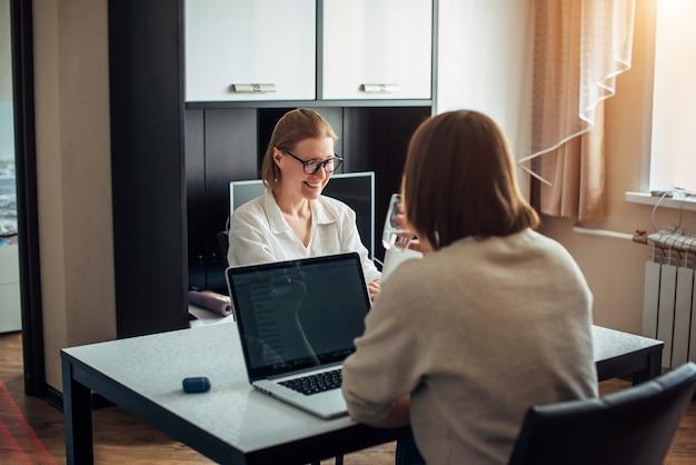 Deux jeunes filles adultes assises à table face à face, travaillant sur des ordinateurs portables à l'intérieur de la maison