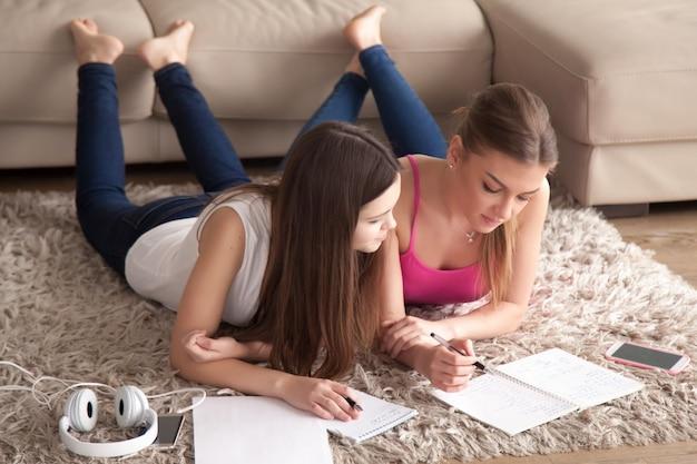 Deux jeunes filles allongées sur un tapis, prenant des notes dans des bloc-notes.