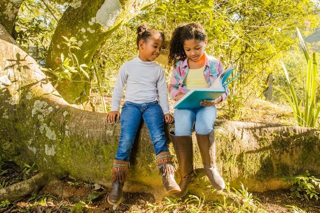 Deux jeunes filles sur l'arbre en train de lire ensemble
