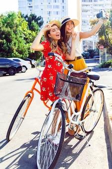 Deux jeunes filles assez élégantes posant près de vélos hipster rétro lumineux et faisant autoportrait