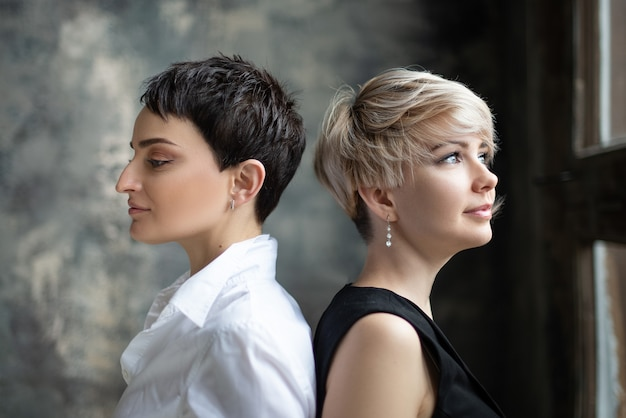 Deux jeunes filles blonde et brune se tiennent le dos