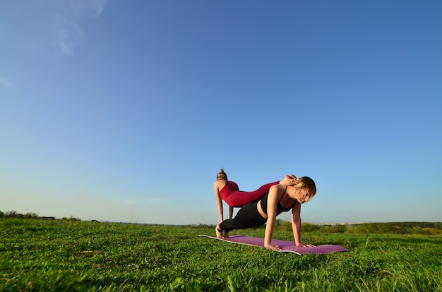 Deux jeunes filles blondes en costume de sport pratiquent le yoga sur une pittoresque colline verdoyante