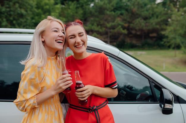 Deux jeunes filles avec des boissons en bouteille à côté de la voiture