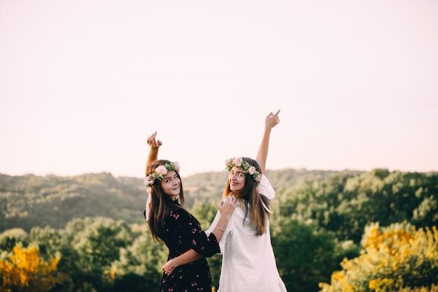 Deux jeunes filles câlin pendant le coucher du soleil sur le terrain avec le concept d'amitié verres à vin