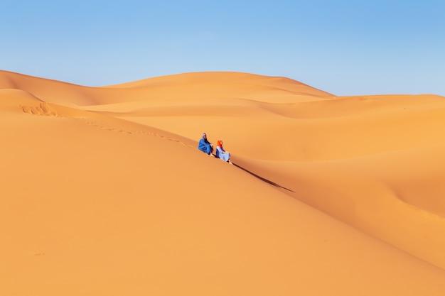Deux jeunes filles en foulard dans le désert du sahara.