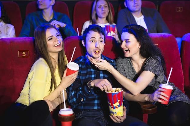 Deux jeunes filles et un gars regardant une comédie dans un cinéma. jeunes amis, regarder un film au cinéma. groupe gens, dans, théâtre, à, pop-corn, et, boissons