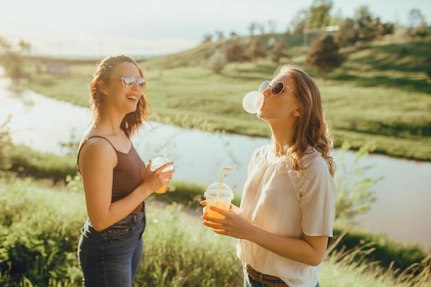 Deux jeunes filles gonflent un chewing-gum. boire du jus de la tasse en plastique, au coucher du soleil, expression faciale positive, en plein air