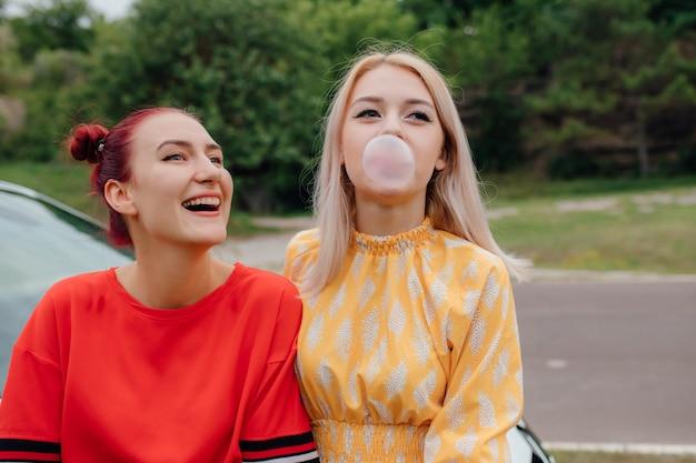Deux jeunes filles heureuse à côté de la voiture