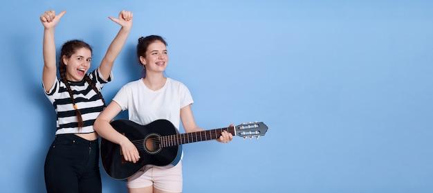 Deux jeunes filles avec jeu de guitare et chante