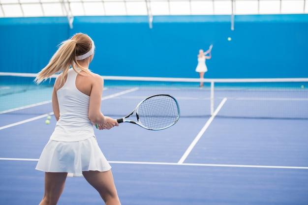 Deux jeunes filles jouant au tennis en cour