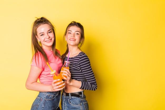 Deux jeunes filles joyeuses de beauté naturelle hipster posant ensemble sur fond jaune