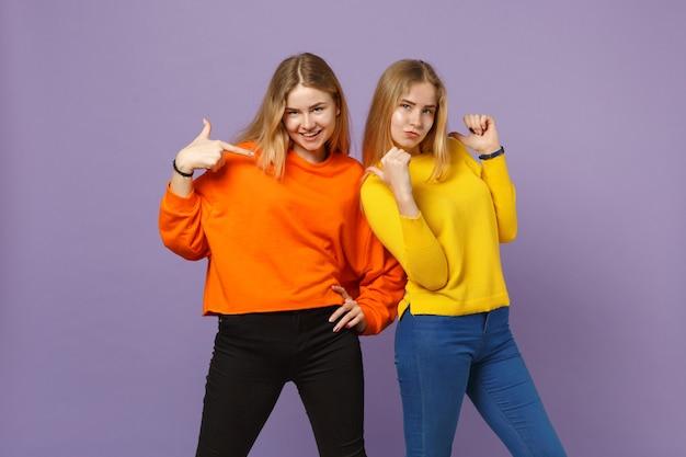 Deux jeunes filles jumelles blondes drôles dans des vêtements colorés vifs pointant du doigt sur elles-mêmes isolées sur un mur bleu violet pastel. concept de mode de vie familial de personnes. .