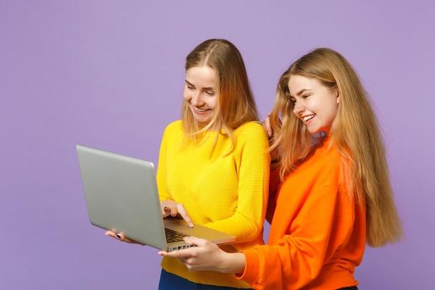 Deux jeunes filles jumelles blondes drôles dans des vêtements colorés vifs tenant, à l'aide d'un ordinateur portable isolé sur un mur bleu violet pastel. concept de mode de vie familial de personnes. .