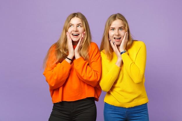 Deux jeunes filles jumelles blondes excitées dans des vêtements colorés vifs mettant les mains sur les joues isolées sur un mur bleu violet pastel. concept de mode de vie familial de personnes.