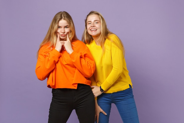 Deux jeunes filles jumelles blondes gaies dans des vêtements colorés vifs pointant des index sur les joues isolées sur un mur bleu violet pastel. concept de mode de vie familial de personnes. .