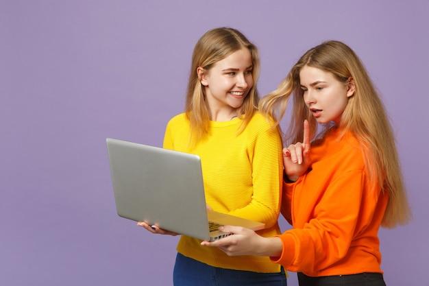 Deux jeunes filles jumelles blondes gaies dans des vêtements colorés vifs tenant à l'aide d'un ordinateur portable isolé sur un mur bleu violet pastel. concept de mode de vie familial de personnes.