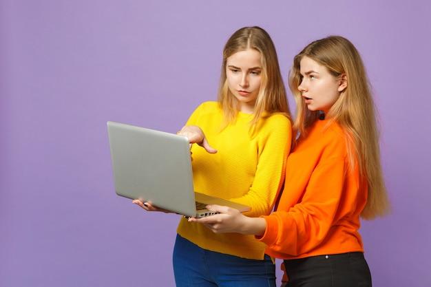 Deux jeunes filles jumelles blondes perplexes dans des vêtements colorés vifs tenant, à l'aide d'un ordinateur portable isolé sur un mur bleu violet pastel. concept de mode de vie familial de personnes.