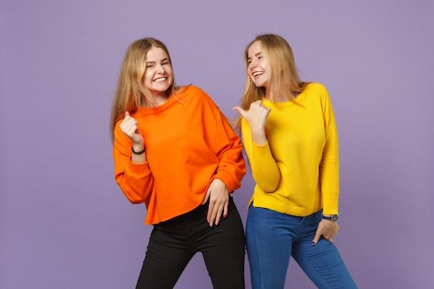 Deux jeunes filles jumelles blondes riantes et joyeuses dans des vêtements colorés vifs pointant le pouce de côté isolés sur un mur bleu violet pastel. concept de mode de vie familial de personnes.