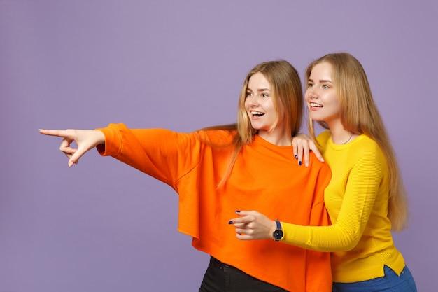 Deux jeunes filles jumelles blondes souriantes dans des vêtements colorés vifs pointant des index de côté isolés sur un mur bleu violet pastel. concept de mode de vie familial de personnes.