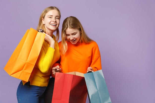 Deux jeunes filles jumelles blondes souriantes dans des vêtements vifs tenant un sac d'emballage avec des achats après le shopping isolés sur un mur bleu violet. concept de mode de vie familial de personnes.