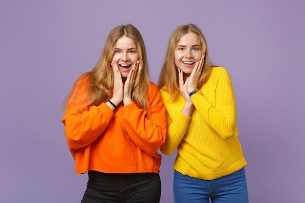 Deux jeunes filles jumelles blondes surprises dans des vêtements colorés vifs mettant les mains sur les joues isolées sur un mur bleu violet pastel. concept de mode de vie familial de personnes. .