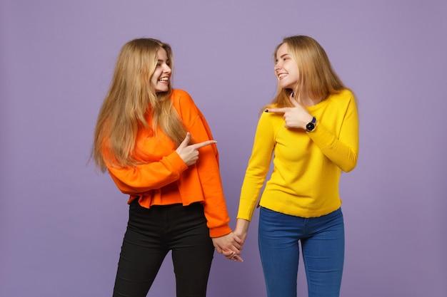 Deux jeunes filles jumelles blondes vêtues de vêtements vifs pointant l'index l'une vers l'autre isolées sur un mur bleu violet pastel. concept de mode de vie familial de personnes.