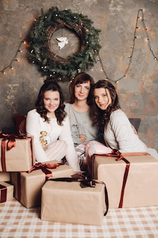 Deux jeunes filles avec leur belle mère adulte assise au milieu de cadeaux de noël emballés contre guirlande de noël