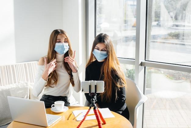 Deux jeunes filles masquées sont assises dans un café et dirigent un blog vidéo. communication avec la caméra.