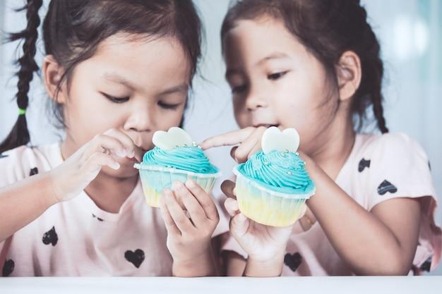 Deux jeunes filles mignonnes asiatiques s'amuser à manger le cupcake bleu ensemble dans le ton de couleur vintage
