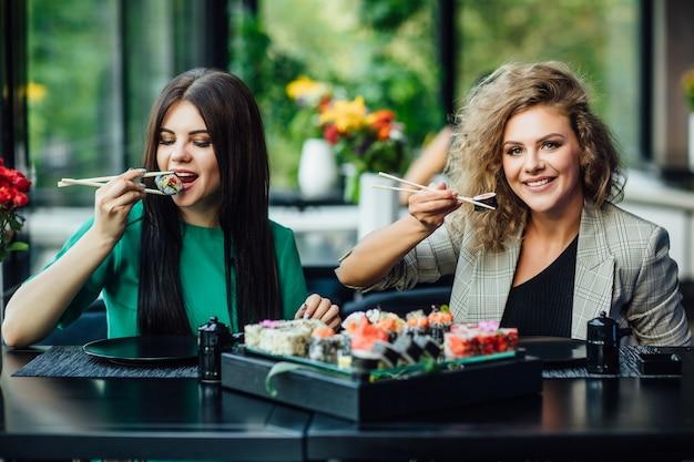 Deux jeunes filles s'assoient au restaurant sur la terrasse d'été et passent du temps amusant avec une assiette philadelphie. notion de sushi.
