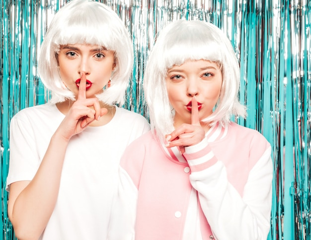 Deux jeunes filles sexy hipster en perruques blanches et lèvres rouges. belles femmes à la mode dans les vêtements d'été.