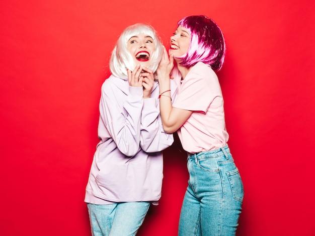 Deux jeunes filles sexy hipster en perruques et lèvres rouges. belles femmes à la mode dans les vêtements d'été. modèles sans soucis posant près du mur rouge en studio deviennent fous