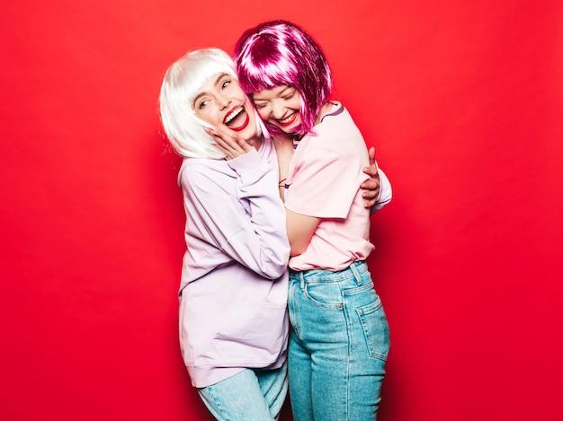 Deux jeunes filles sexy hipster souriant en perruques blanches et lèvres rouges. belles femmes à la mode dans des vêtements d'été. modèles sans soucis posant près du mur rouge en studio devenant fou